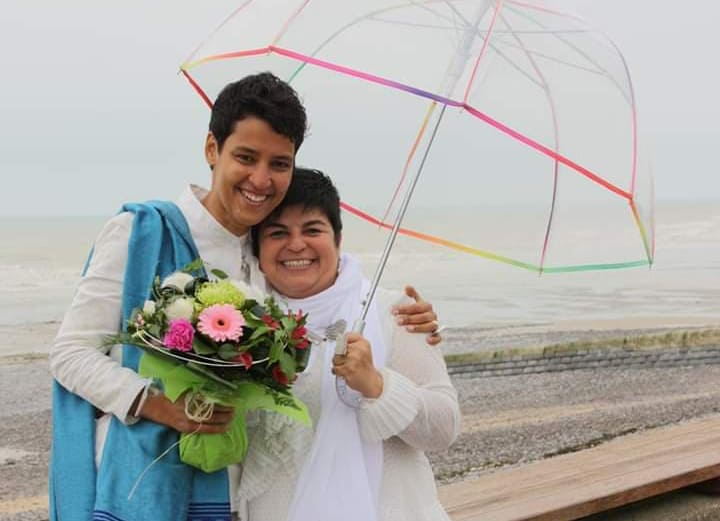 Photo shows two women holding up an umbrella and with flowers in their hands.